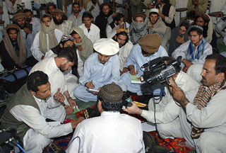 Baitullah Mehsud, the Taliban chief in Pakistan, center with his back to the camera. {Image: PakAlert}