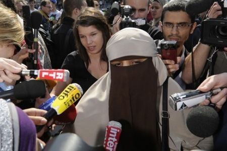 Kenza Drider, a burqa-wearing French Muslim, is surrounded by media in the French capital.
