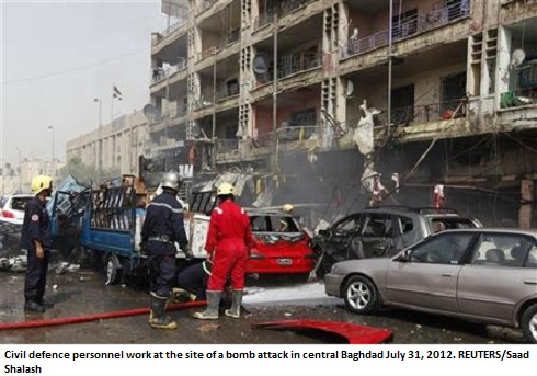 Civil defence personnel work at the site of a bomb attack in central Baghdad