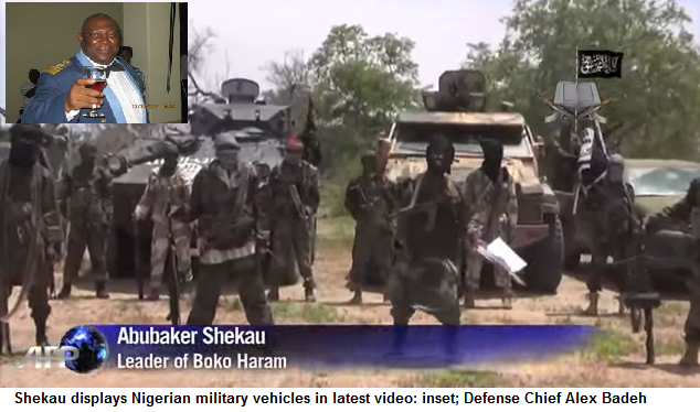 Shekau stands posing infront of Nigerian military vehicles