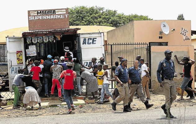 BLIND EYE: Police officers stroll away from a crowd looting a shop in White City, Soweto yesterday. In an official statement, the South African Police Service said that its officers were taking strong action and would not allow lawlessness to prevail  Image by: ALON SKUY