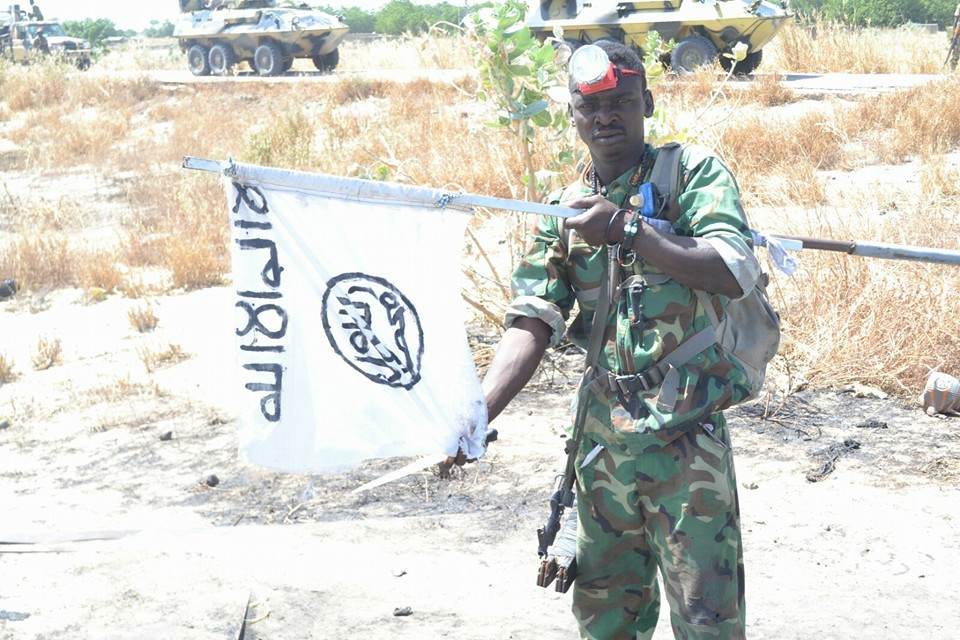 A soldier destroying Boko Haram terrorists flag recovered from the camp.