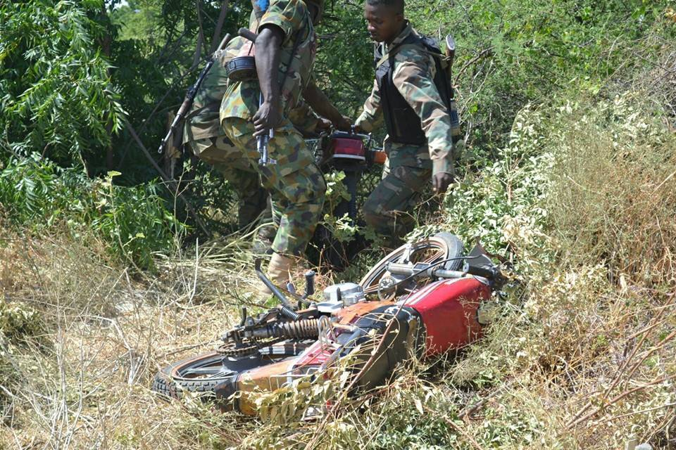 Soldiers recovering abandoned motorcycles.