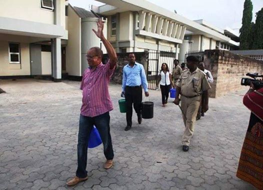 Government official carries bucket of water in jail
