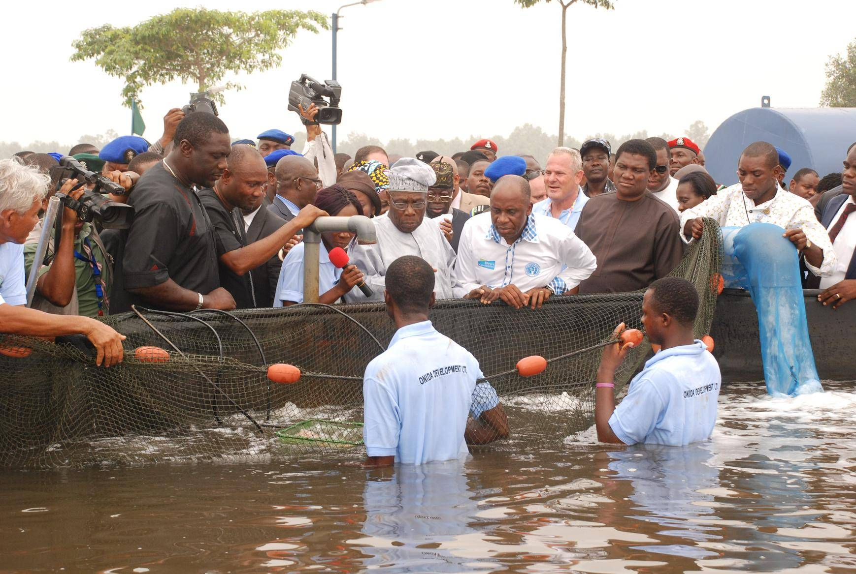 AGRIC 007, FMR PRESIDENT OBASANJO, GOV AMAECHI AND OTHERS OBSERVING THE OPERATIONS OF THE BUGUMA FISH FARM